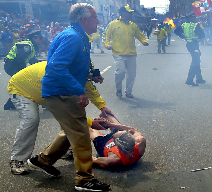 Il signor Bill Iffrig scaraventato a terra dalla prima esplosione mentre la seconda deflagra all'arrivo della Maratona di Boston 2013